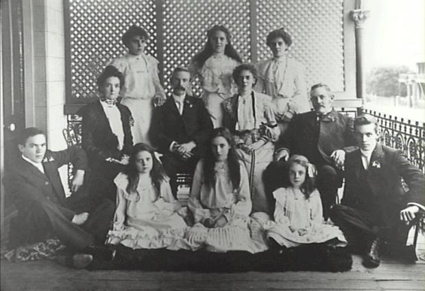 Family photograph on verandah above Argyle Street, looking west.  Man  seated on right in second row is Charles Thomas White man .