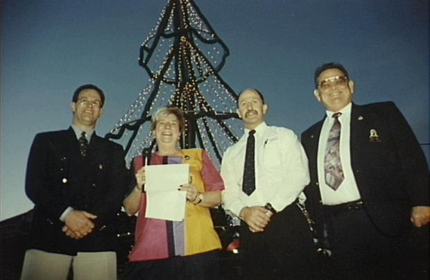 Official turning on of lights on Christmas tree in Camden, decorating a flag pole. 1996