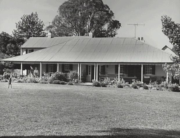 The front section was built by Charles Hook before 1826 and the two storey section by Thomas Hassall after he purchased Denbigh about 1826. Since renovated. Mrs Lesley McIntosh ( owner) standing on verandah. Copyright: Camden Historical Society.